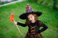 准备的万圣夜 邪恶的巫婆的衣服的女孩清洗草坪犁耙 免版税库存图片
