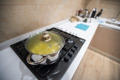 准备的可口晚餐食物面团或汤或者炖煮的食物在大钢平底锅,凉快的下来在盒盖,立场下在气体火炉烹饪器材 免版税库存照片