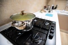 准备的可口晚餐食物面团或汤或者炖煮的食物在大钢平底锅,凉快的下来在盒盖,立场下在气体火炉烹饪器材 库存照片
