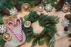准备的圣诞节假日 圣诞节结构的花圈、棒棒糖、枝杈、干桔子和雪花 妇女准备a 免版税库存照片