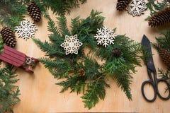 准备的圣诞节假日 圣诞节结构的花圈、装饰、干桔子、枝杈和雪花 妇女准备一wreat 库存照片