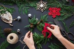 准备的圣诞节假日 花圈、装饰、麻线、枝杈和雪花圣诞节车间  妇女准备一个花圈 名列前茅v 免版税库存图片