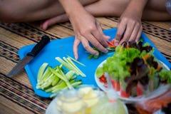 准备的妇女烹调在砧板的沙拉 在蓝色砧板的新鲜蔬菜对烹调沙拉 免版税库存照片