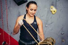 准备的安全带的登山人女孩在八个结中栓绳索和上升,手看法  免版税图库摄影