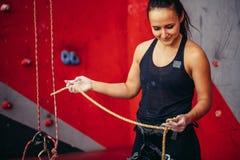 准备的安全带的登山人女孩在八个结中栓绳索和上升,手看法  库存照片