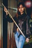 准备的皮夹克的女孩演奏台球 免版税图库摄影
