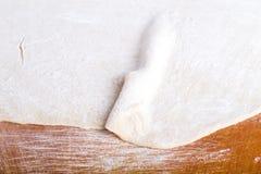 准备的过程lagman或薄饼 在老光的未加工的面团 免版税库存图片