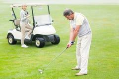 准备的高尔夫球运动员与在他后的伙伴 免版税库存图片