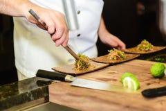 准备盘的烹饪厨师在餐馆 免版税库存照片