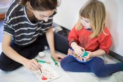 准备红色油漆的妇女和孩子 免版税库存照片