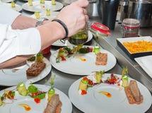 准备红色金枪鱼和三文鱼齿垢的厨师 免版税库存图片