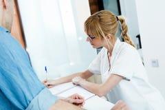 准备纸的美容师为他的男性客户签字在诊所招待会 库存照片