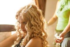 准备美丽的新娘的美发师在婚礼前在一个早晨 免版税图库摄影