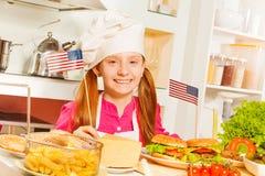 准备美国食物的厨师制服的愉快的女孩 免版税库存图片