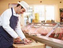 准备肉的屠户在商店 免版税库存照片