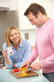 准备膳食的成熟夫妇在国内厨房里 库存照片