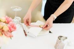准备花婚礼装饰的卖花人在室外餐馆 没有面孔,在假日布置的桌 库存图片