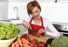准备菜沙拉用莴苣红萝卜和切蕃茄的愉快的妇女在家厨房 免版税库存照片