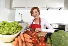 准备菜沙拉用莴苣红萝卜和切蕃茄的愉快的妇女在家厨房 图库摄影