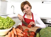 准备菜沙拉用莴苣红萝卜和切蕃茄的愉快的妇女在家厨房 免版税库存图片