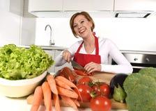 准备菜沙拉用莴苣红萝卜和切蕃茄的愉快的妇女在家厨房 免版税图库摄影