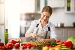 准备菜沙拉的愉快的妇女在厨房里 免版税库存图片