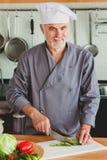 准备菜的友好的厨师在他的厨房里 库存照片