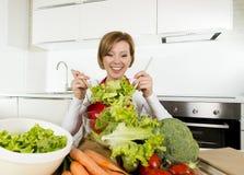 准备菜色拉盘微笑的现代厨房的年轻美丽的家庭厨师妇女愉快 免版税库存照片
