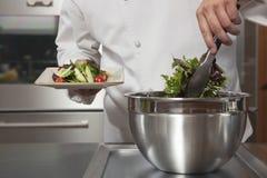 准备蔬菜叶的厨师在商业厨房里 库存图片