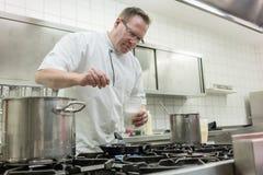 准备薄煎饼点心倾吐的面团的厨师入平底锅在厨房里 库存图片