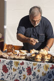 准备薄饼用熟香肠和porchetta三明治的Ederly人 免版税库存图片