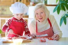 准备薄饼的祖母和孙女 免版税库存图片
