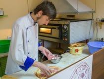 准备薄饼的年轻厨师 图库摄影
