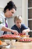 准备蛋糕的母亲和儿子在厨房里 免版税库存图片