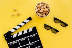 准备观看影片 Clapperboard、玻璃和玉米花在黄色背景顶视图 免版税库存图片