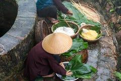 准备越南的妇女做钟结块,越南月球新年Tet食物室外由老井和池塘 免版税图库摄影