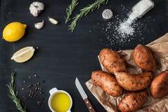准备迷迭香烤了与橄榄油、柠檬、盐、胡椒和大蒜的白薯 免版税库存图片