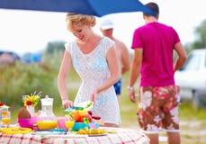 准备野餐桌的妇女在夏天公园 库存照片
