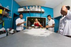 准备面团用面粉,profesional厨师的小组愉快的年轻亚裔点心师工作在厨房 免版税库存照片
