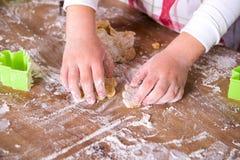 准备面团的儿童厨师 特写镜头女孩的厨师的手用面团和面粉,准备过程的食物 免版税库存图片