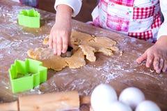 准备面团的儿童厨师 特写镜头女孩的厨师的手用面团和面粉,准备过程的食物 免版税库存照片