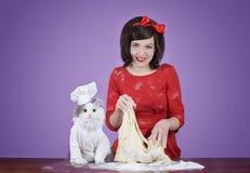 准备面团的少妇和一只蓬松猫 库存图片