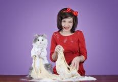 准备面团的少妇和一只蓬松猫 免版税图库摄影