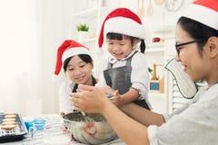 准备面团的愉快的亚洲家庭穿戴圣诞老人帽子,烘烤咕咕声 库存图片