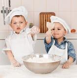 准备面团的愉快的矮小的厨师在厨房里 免版税图库摄影