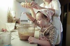 准备面团的母亲和女儿在厨房里 库存图片