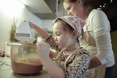 准备面团的母亲和女儿在厨房里 免版税图库摄影