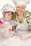 准备面团的母亲和女儿 库存图片