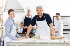 准备面团的确信的男性和女性厨师在 图库摄影