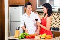 准备食物的亚洲夫妇在国内厨房里 免版税图库摄影